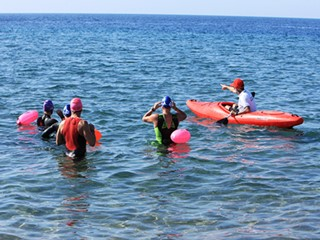A group looking out to sea during open water swimming training