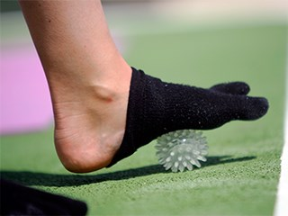 streching feet ligaments with massage ball in release and unwind