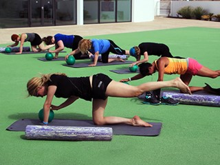 a class doing pilates infront of cls arena at club la santa