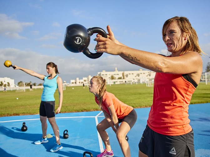 Girl lifting kettle bell during Function training class