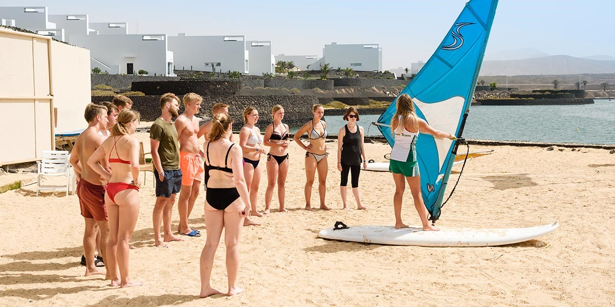 Group of young people getting some windsurfing instructions from a Green teamer